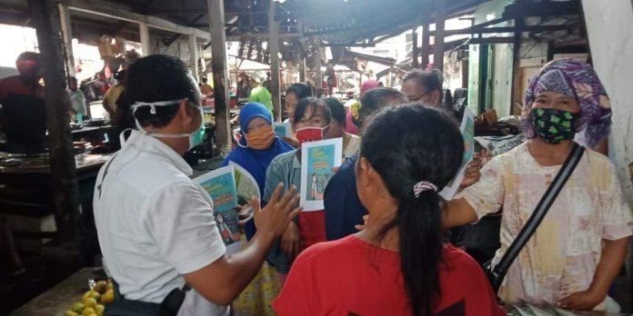 Kepala Dinkes dr Erman Paputungan saat membagikan liflet dan himbauan langsung kepada warga dipasar Lolak qqq